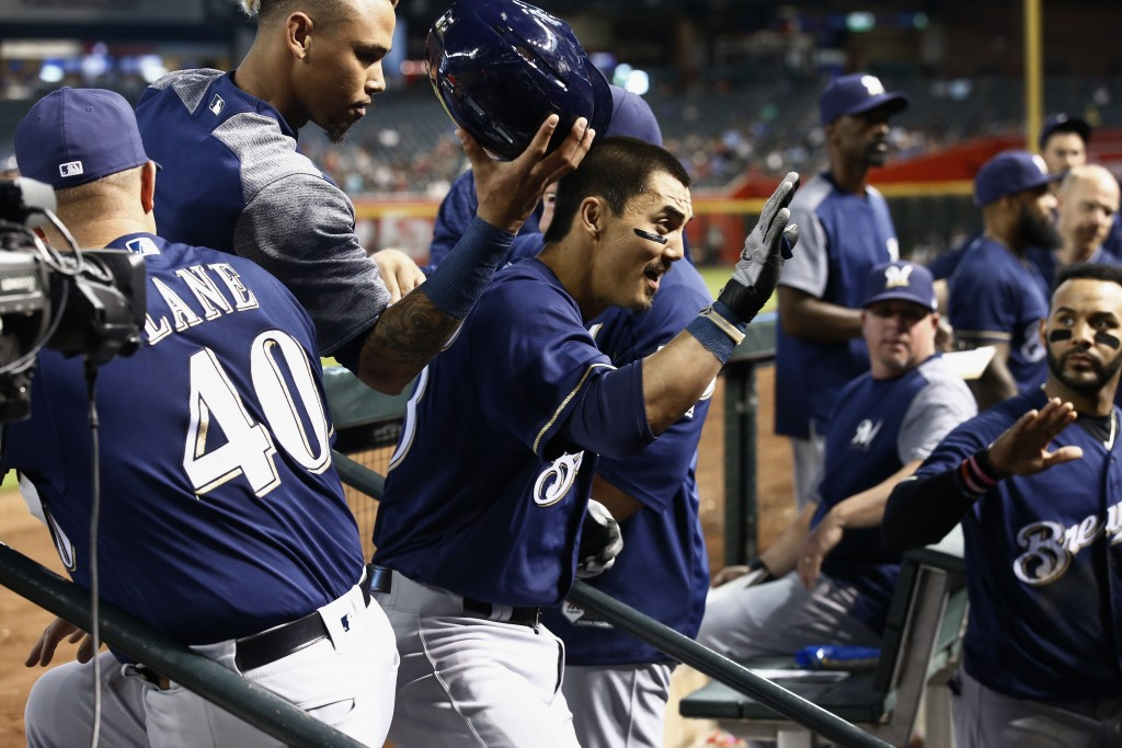 Milwaukee Brewers' Tyler Saladino, middle, celebrates his home run against the Arizona Diamondbacks with coach Jason Lane (40), Orlando Arcia, top lef