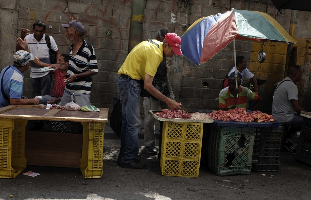 In this May 11, 2018 photo, street vendors selling beef bones wait for customers, in Caracas, Venezuela. The May 20 presidential election plays out as