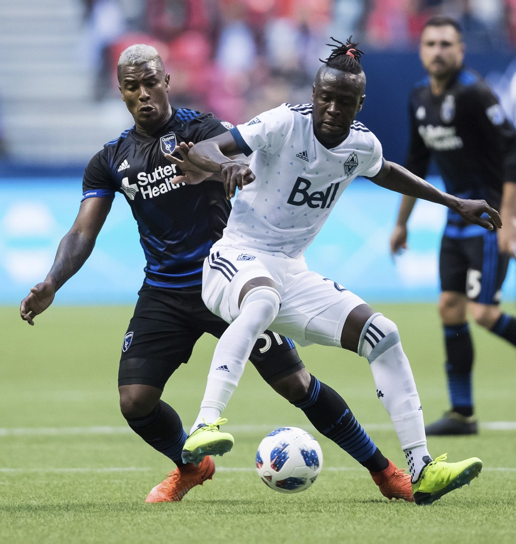Vancouver Whitecaps' Kei Kamara, front right, and San Jose Earthquakes' Harold Cummings vie for control of the ball during the first half of an MLS so