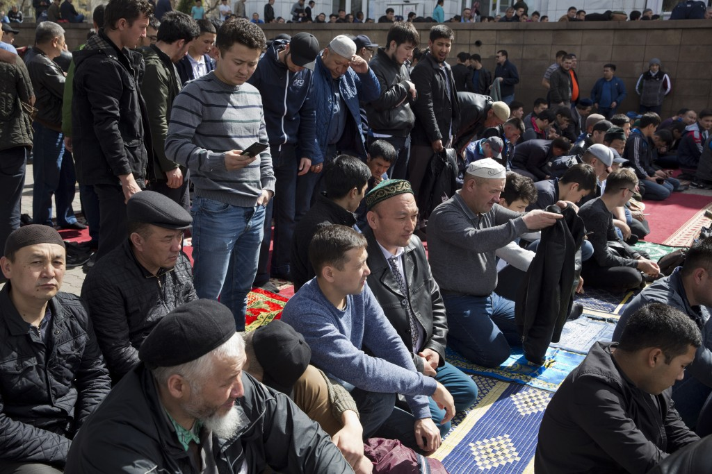 In this March 30, 2018, photo, Omir Bekalic, center, prepares to pray at a mosque in Almaty, Kazakhstan. Since 2016, Chinese authorities in the heavil