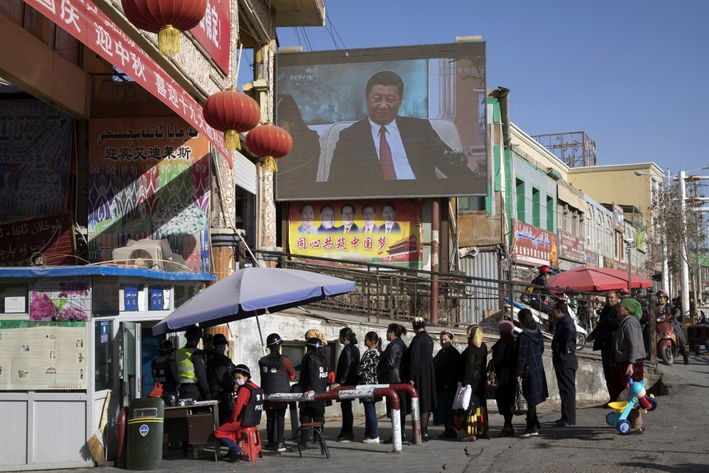 FILE - In this Nov. 3, 2017, file photo, residents walk through a security checkpoint into the Hotan Bazaar where a screen shows Chinese President Xi