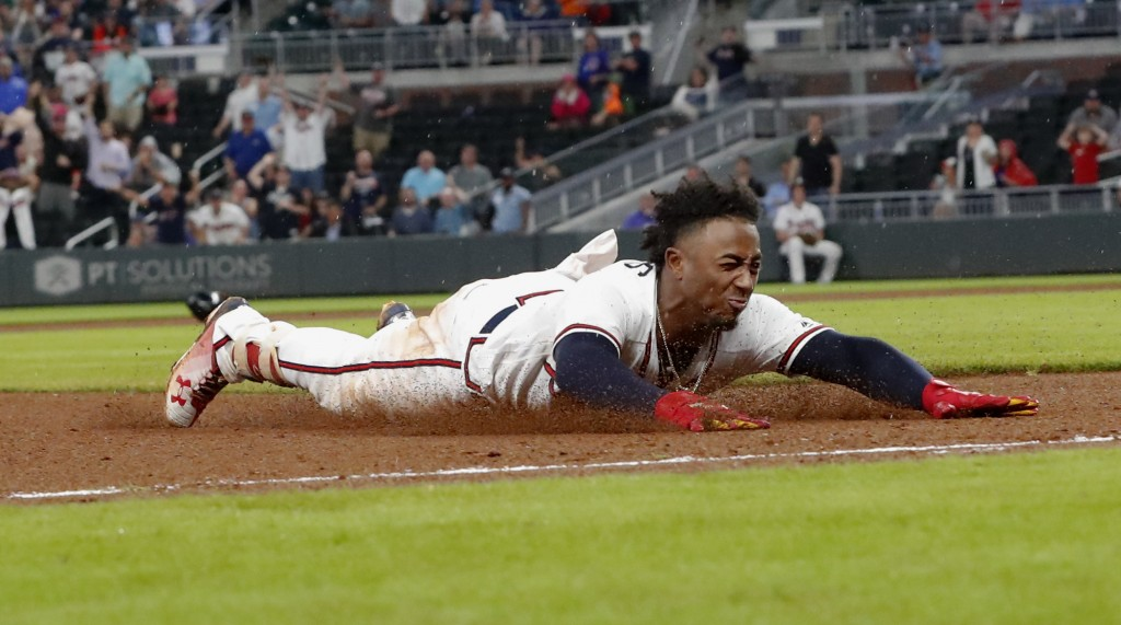 Atlanta Braves' Ozzie Albies slides into third base with a triple during the eighth inning of the team's baseball game against the Chicago Cubs on Wed