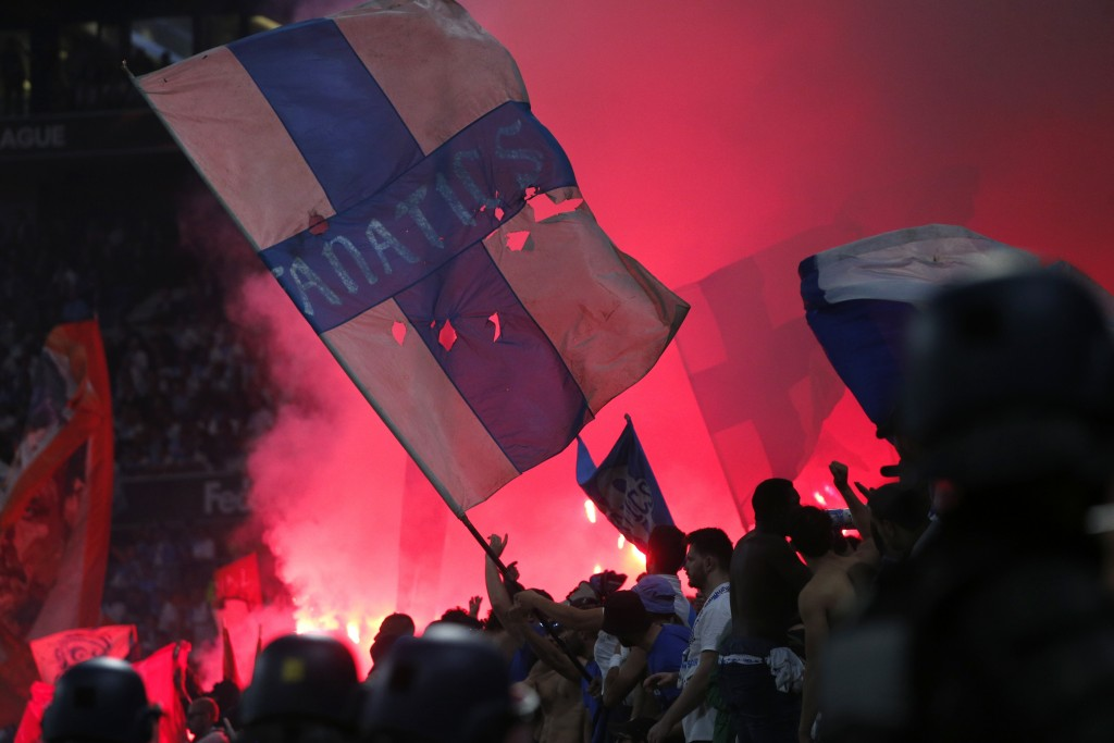 Fans set off flares during the Europa League Final soccer match between Marseille and Atletico Madrid at the Stade de Lyon in Decines, outside Lyon, F