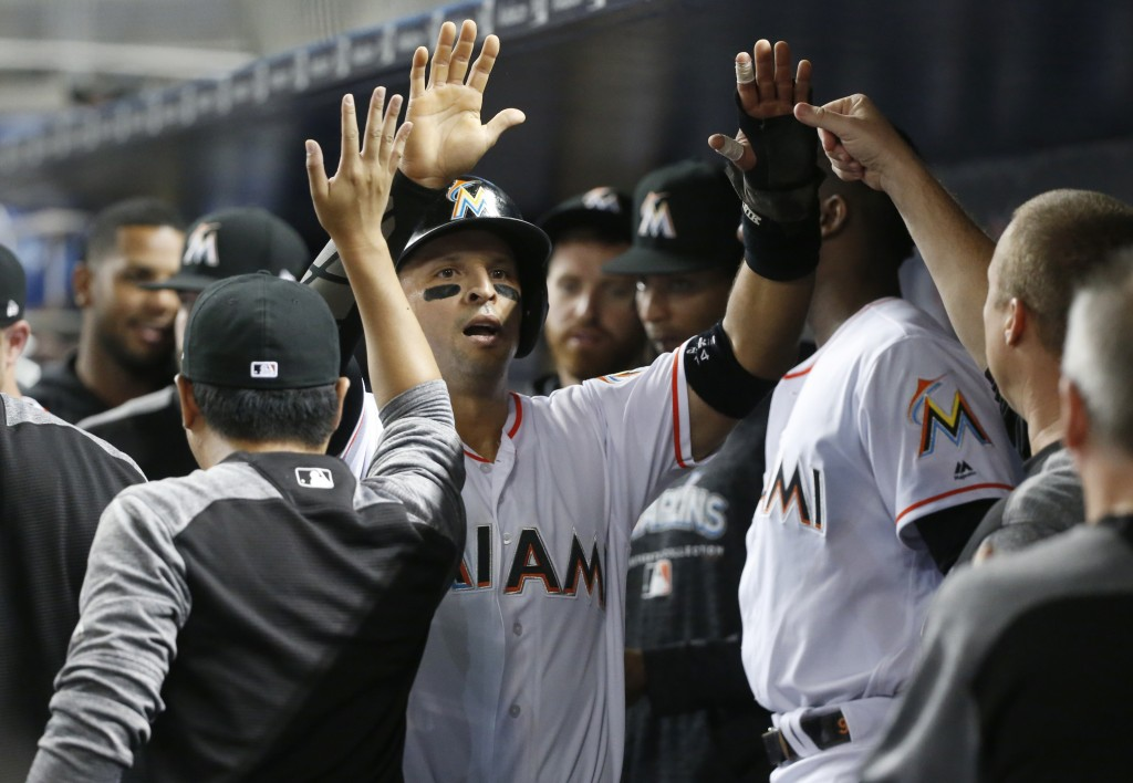 Miami Marlins' Martin Prado, center, is congratulated by teammates after scoring on a single by Brian Anderson during the first inning of a baseball g