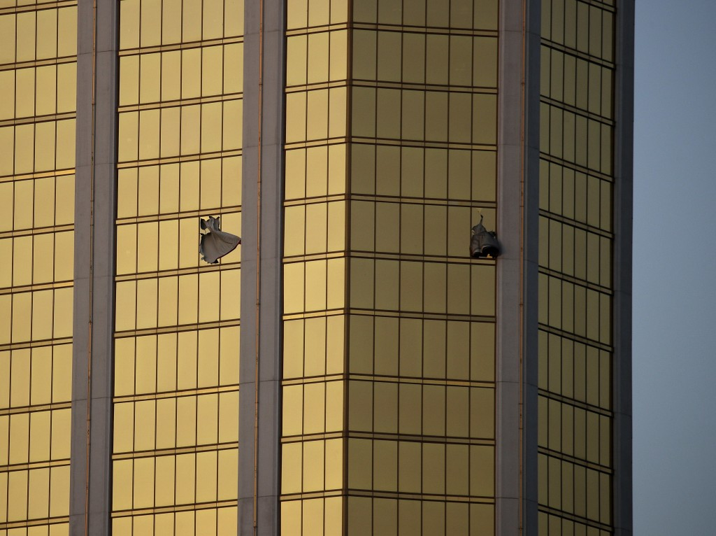FILE - In this Monday, Oct. 2, 2017 file photo, drapes billow out of broken windows at the Mandalay Bay resort and casino on the Las Vegas Strip, foll
