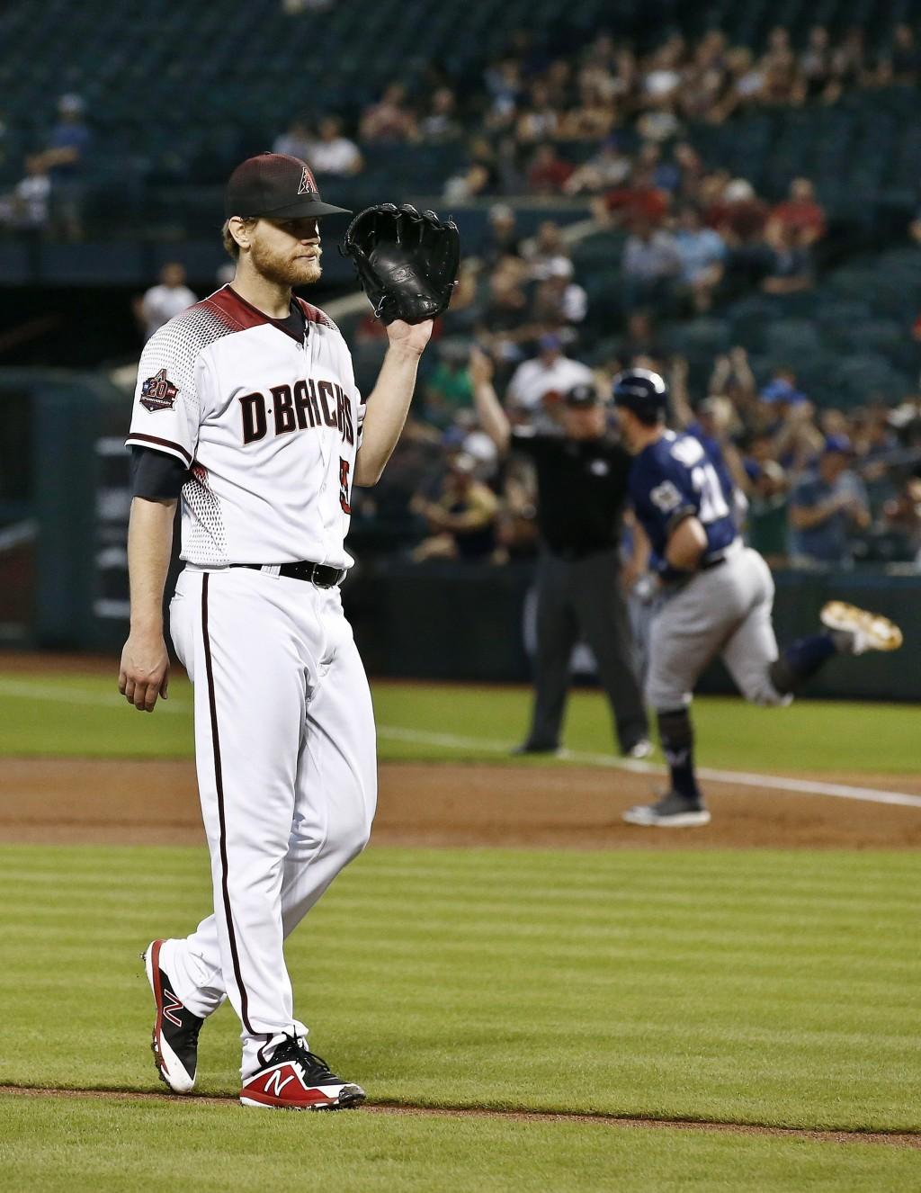Arizona Diamondbacks starting pitcher Matt Koch, left, waits for a new baseball after giving up a two-run home run to Milwaukee Brewers' Travis Shaw,