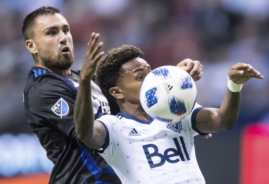 Vancouver Whitecaps' Yordy Reyna, right, attempts to gain control of the ball as San Jose Earthquakes' Jimmy Ockford defends during the second half of
