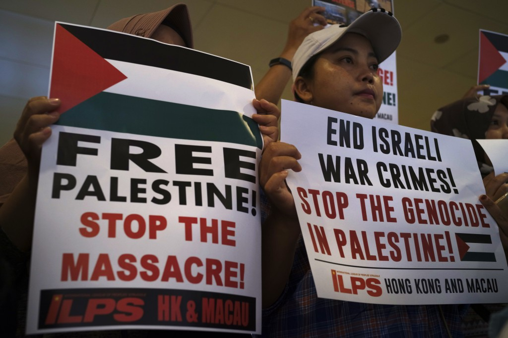 Protesters hold placards outside the Israeli Embassy to condemn the Gaza Strip violence which left dozens dead, in Hong Kong Thursday, May 17, 2018. T