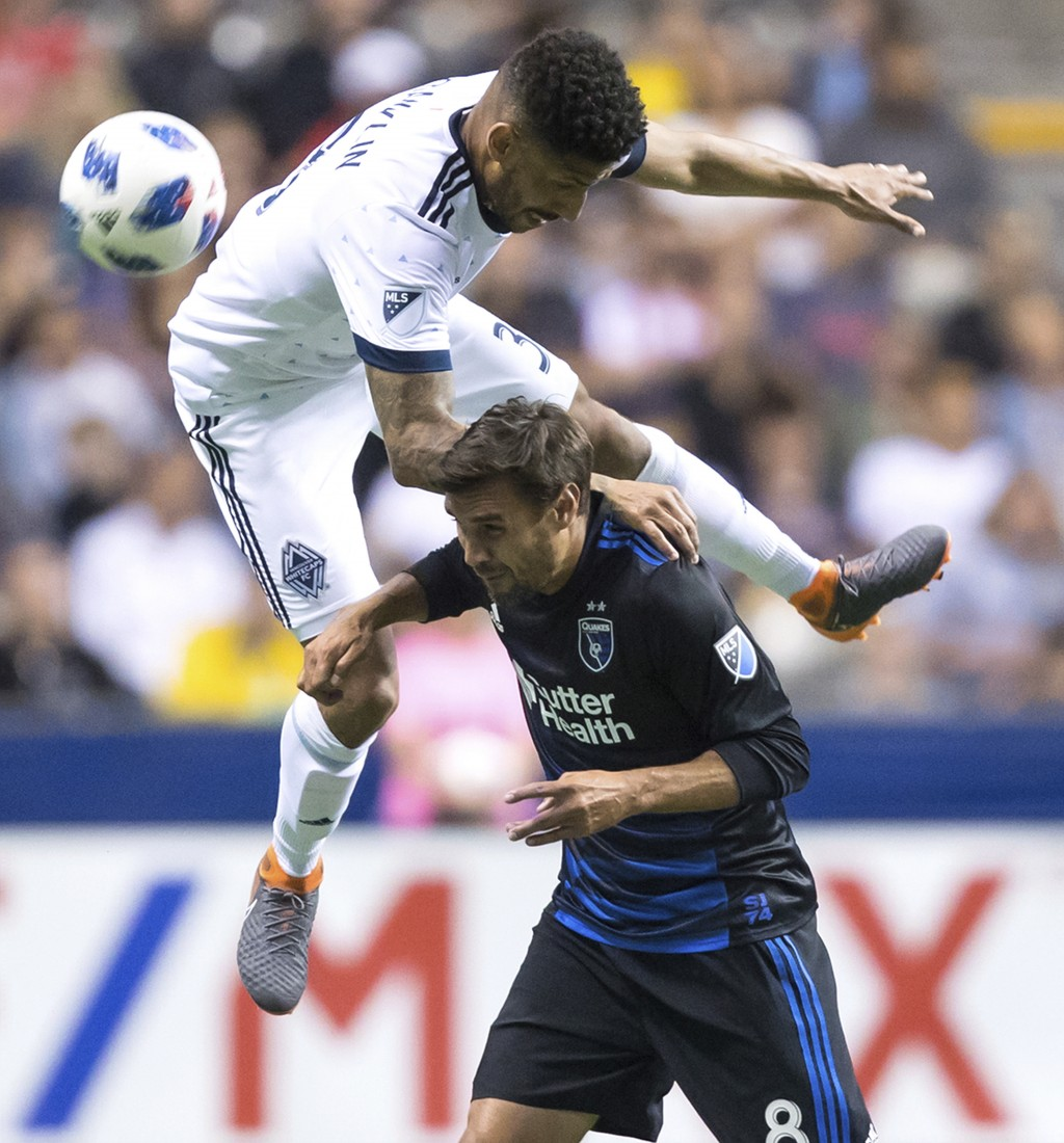 Vancouver Whitecaps' Sean Franklin, top, and San Jose Earthquakes' Chris Wondolowski vie for the ball during the second half of an MLS soccer match in