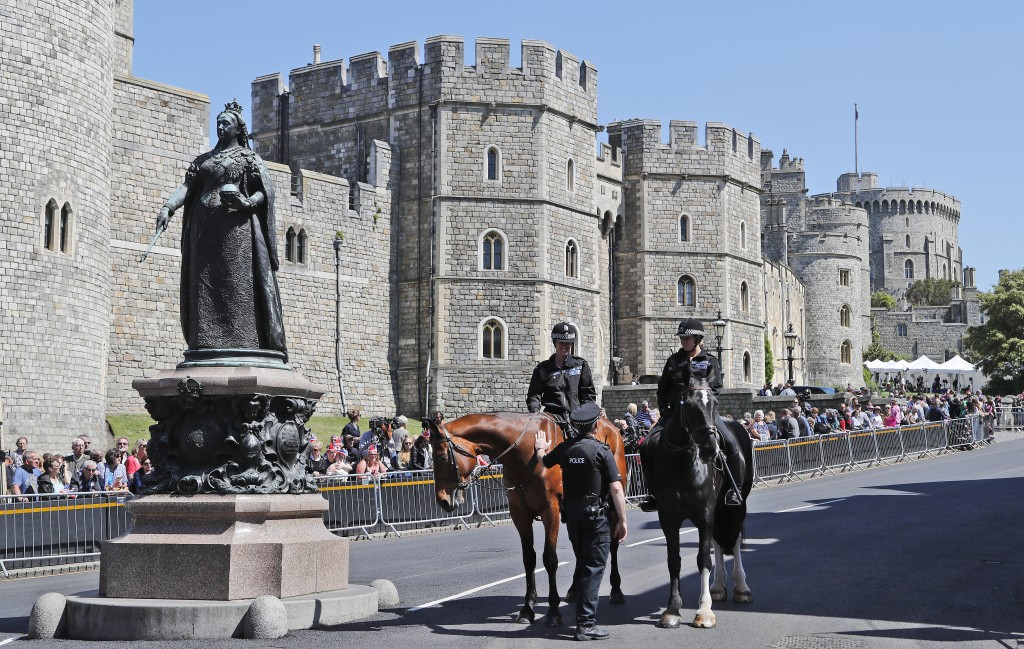 Mounted police officers patrol in front of Windsor Castle before a rehearsal for the procession of the upcoming wedding of Britain's Prince Harry and