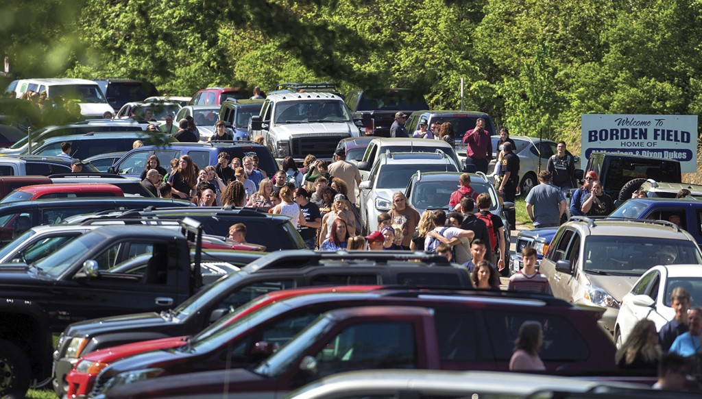 Parents wait down the road to meet their children following a shooting at Dixon High School Wednesday, May 16, 2018, in Dixon, Ill. A 19-year-old who