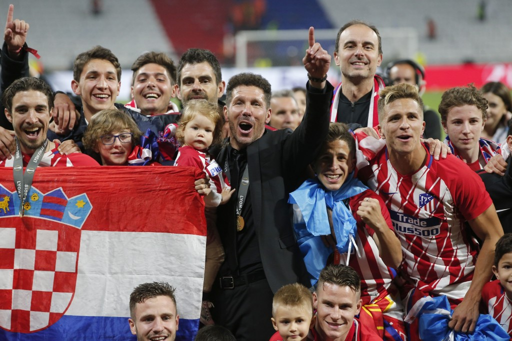 Atletico's head coach Diego Simeone, in black suit, celebrates with his players after winning the Europa League Final soccer match between Marseille a