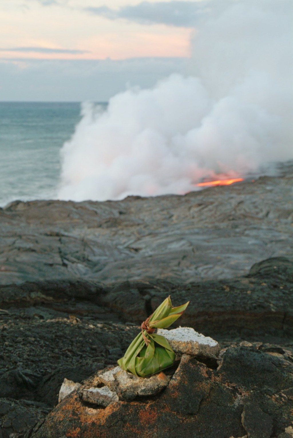 FILE - In this June 22, 2004 file photo, an offering to Pele, goddess of Hawaiian volcanoes, adorns the cliffs above the newest lava flow from Kilauea