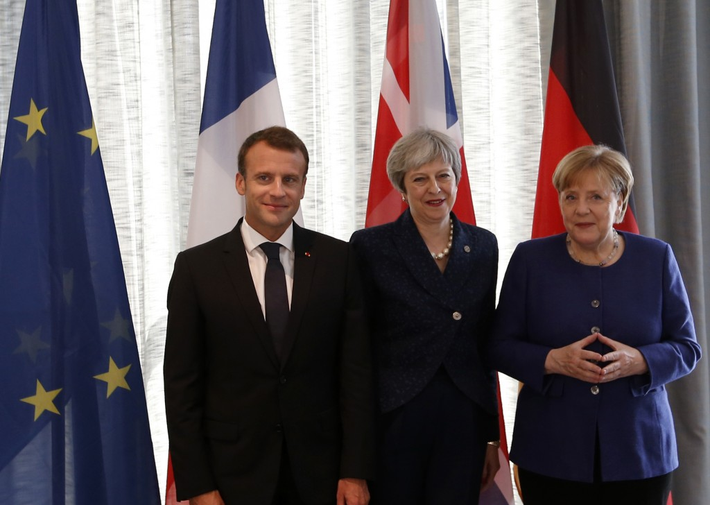 German Chancellor Angela Merkel, right, French President Emmanuel Macron, left, and British Prime Minister Theresa May pose prior meeting at a hotel o