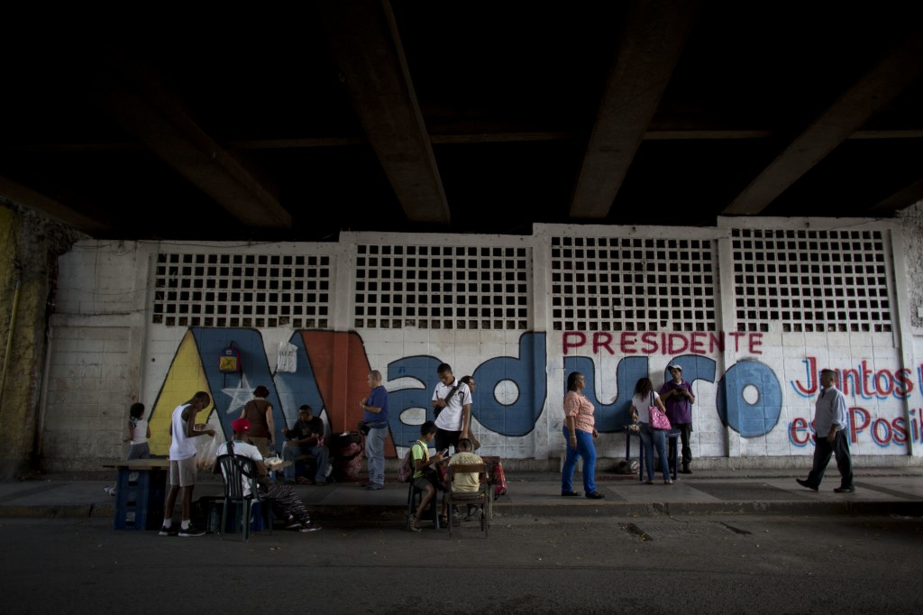 "A wall is covered with the Spanish words ""Maduro President"" ahead of the presidential election where vendors have their tables set up on the sidewalk"