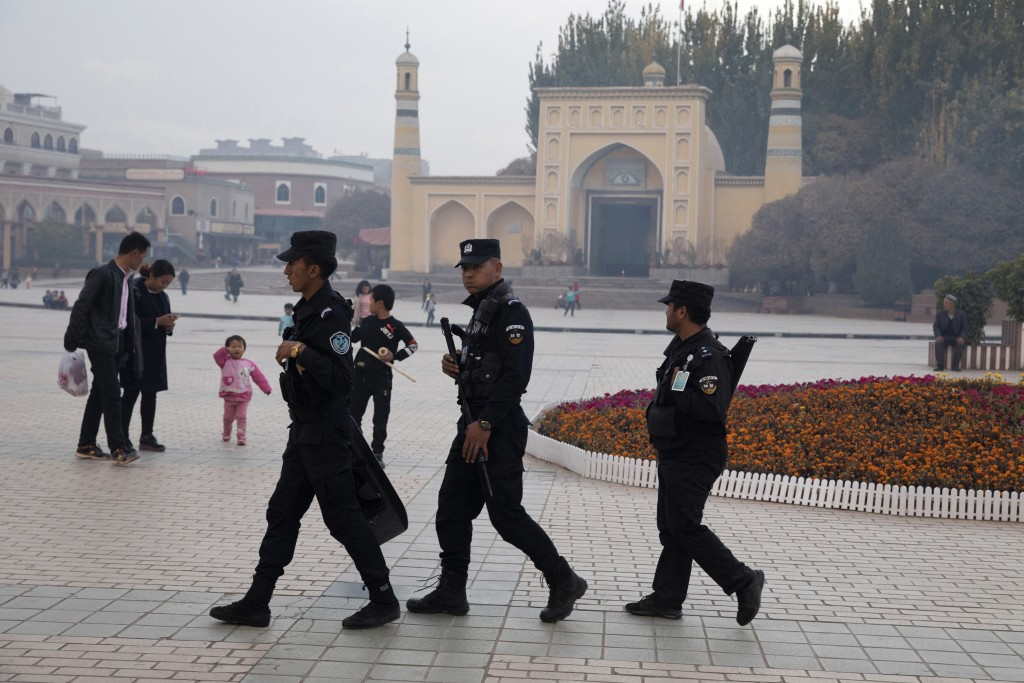 FILE - In this Nov. 4, 2017 file photo, Uighur security personnel patrol near the Id Kah Mosque in Kashgar in western China's Xinjiang region. Since 2