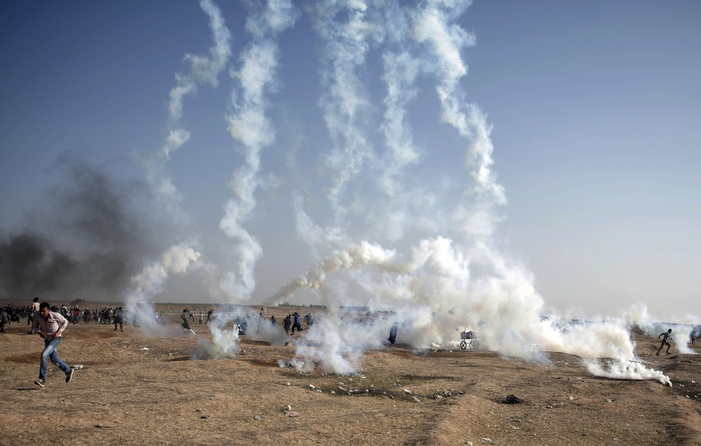 FILE - In this Tuesday, May 15, 2018 file photo, Palestinian protesters run from teargas fired by Israeli troops at the Gaza Strip's border with Israe