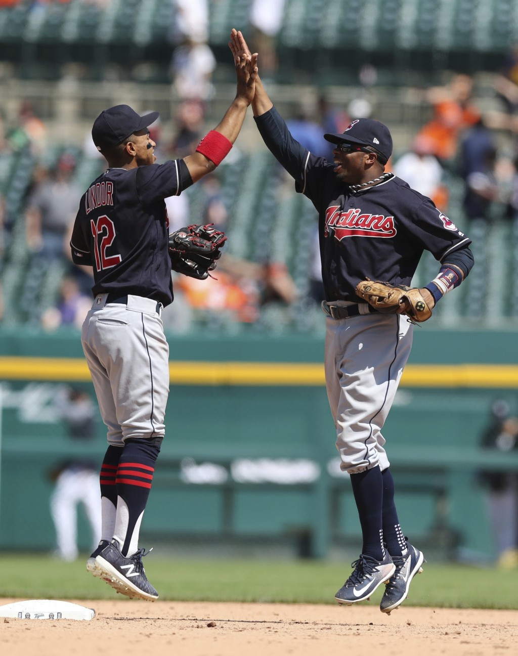Cleveland Indians shortstop Francisco Lindor (12) and center fielder Rajai Davis celebrate the team's 6-0 win over the Detroit Tigers after a baseball