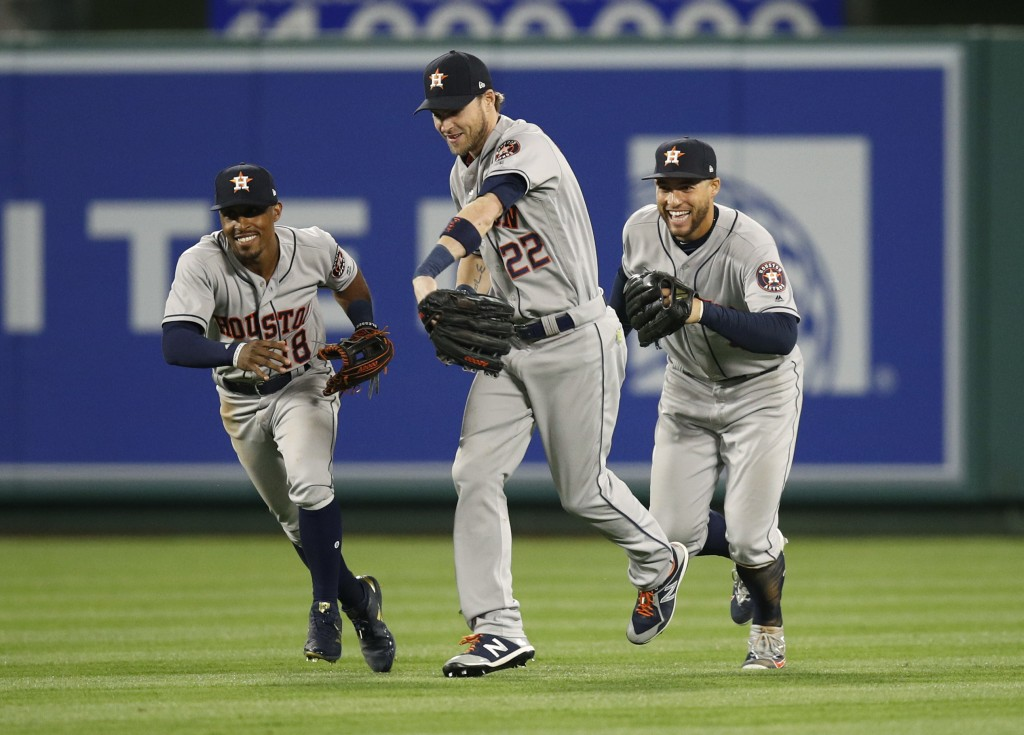 Houston Astros' Tony Kemp, Josh Reddick and George Springer, from left, celebrate the team's 2-0 win over the Los Angeles Angels in a baseball game We