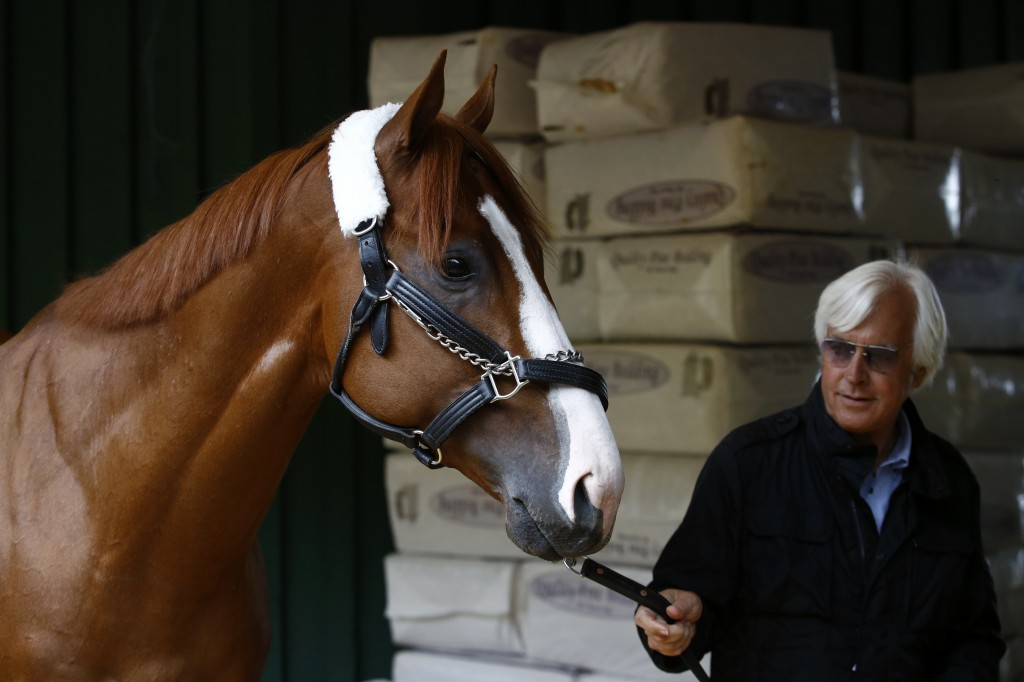 Kentucky Derby winner Justify walks in a barn with trainer Bob Baffert, Wednesday, May 16, 2018, after Justify's arrival at Pimlico Race Course in Bal
