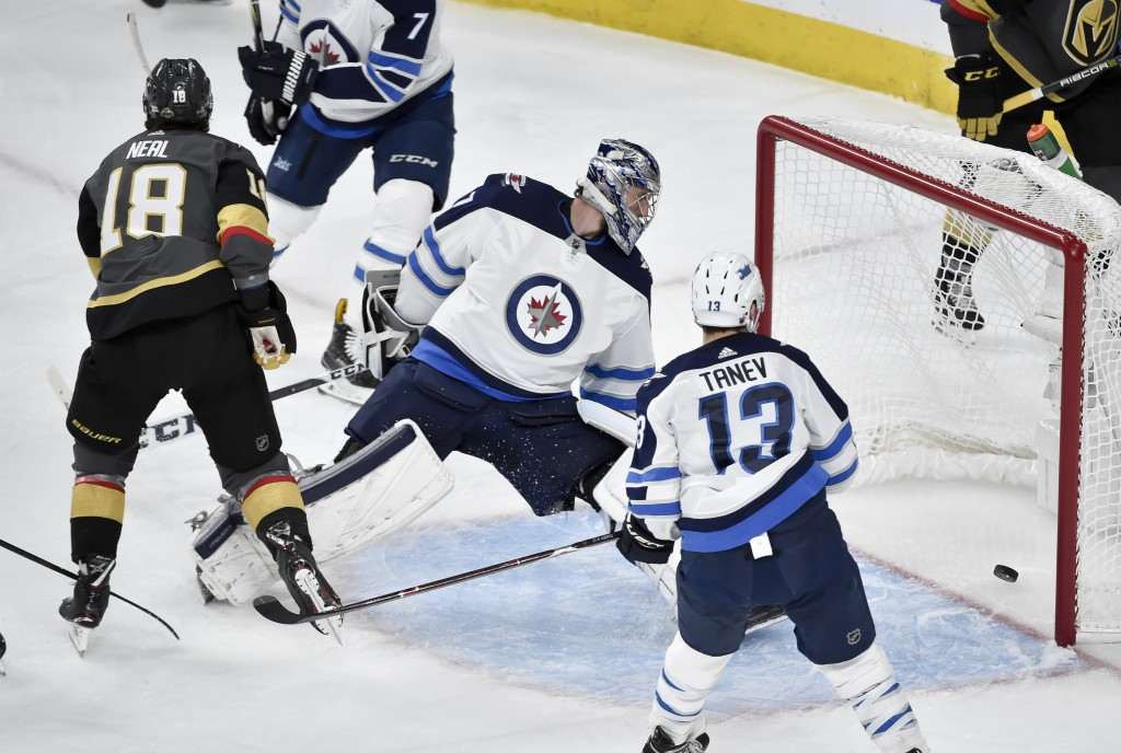 Vegas Golden Knights left wing James Neal, left, scores past Winnipeg Jets goaltender Connor Hellebuyck as Brandon Tanev watches during the second per