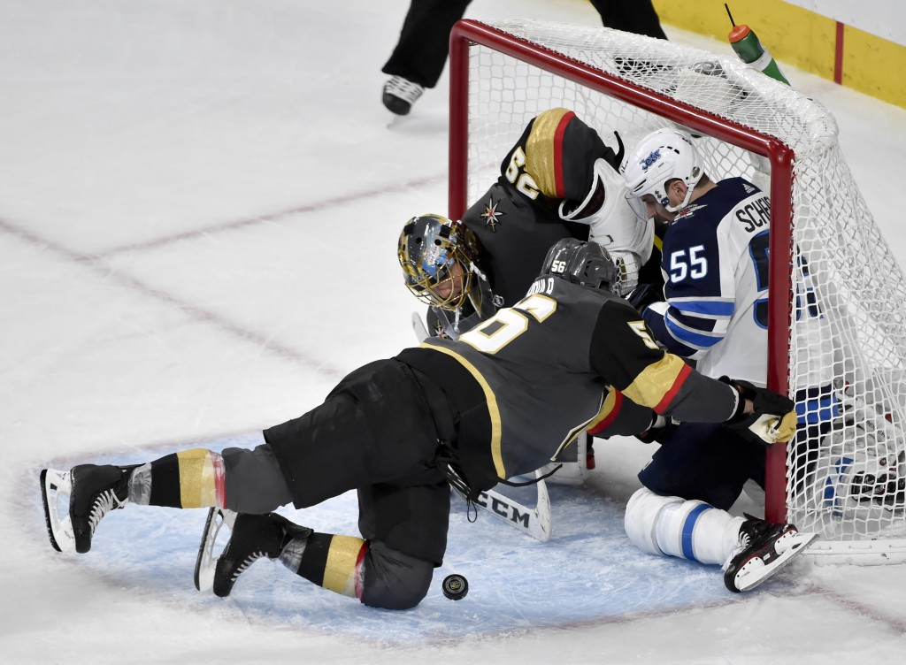 Winnipeg Jets center Mark Scheifele, right, crashes into Vegas Golden Knights goaltender Marc-Andre Fleury and left wing Erik Haula, left, during the