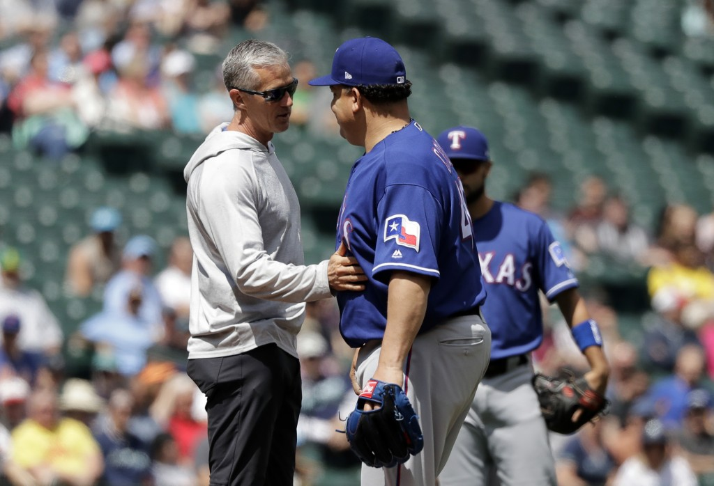 Texas Rangers trainer Kevin Harmon, left, touches the stomach of starting pitcher Bartolo Colon after Colon was hit with a ball hit by Seattle Mariner