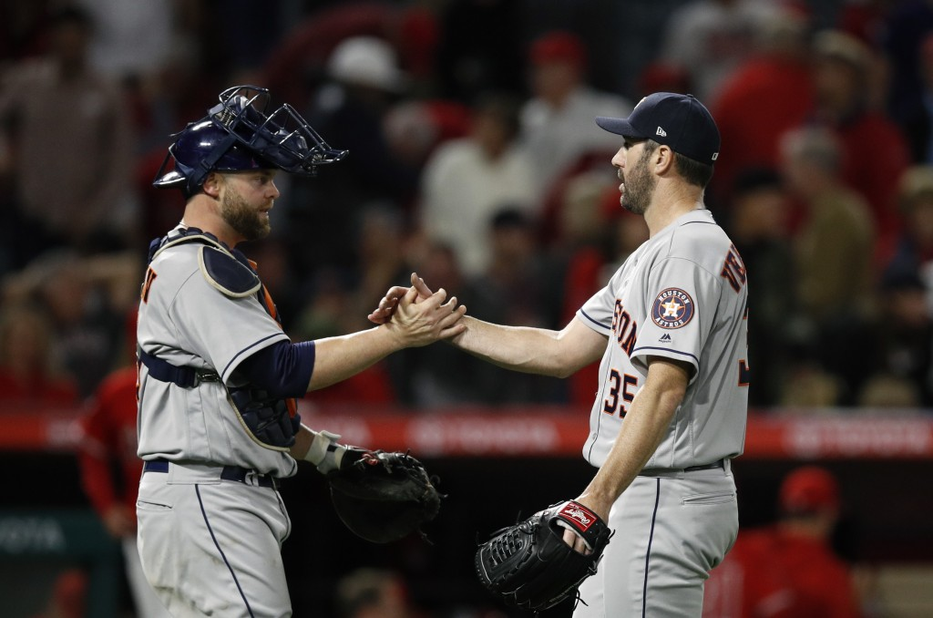 Houston Astros catcher Brian McCann, left, and starting pitcher Justin Verlander celebrate the team's 2-0 win over he Los Angeles Angels in a baseball...