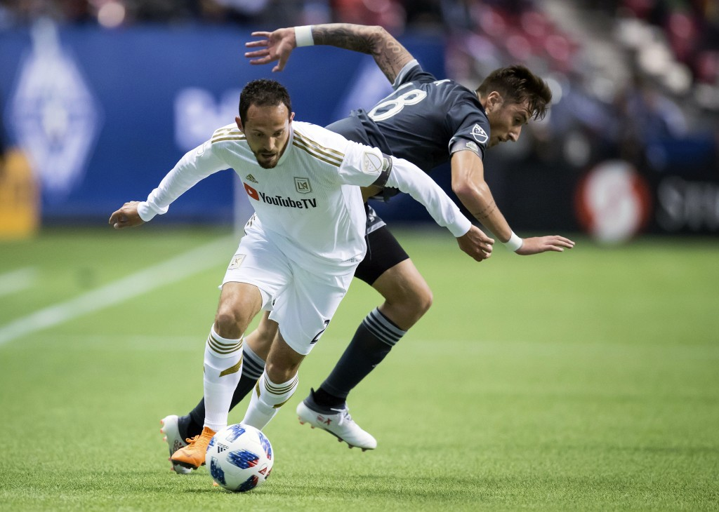 FILE - In this April 13, 2018, file photo, Los Angeles FC's Marco Urena, front, moves the ball past Vancouver Whitecaps' Jose Aja during the first hal