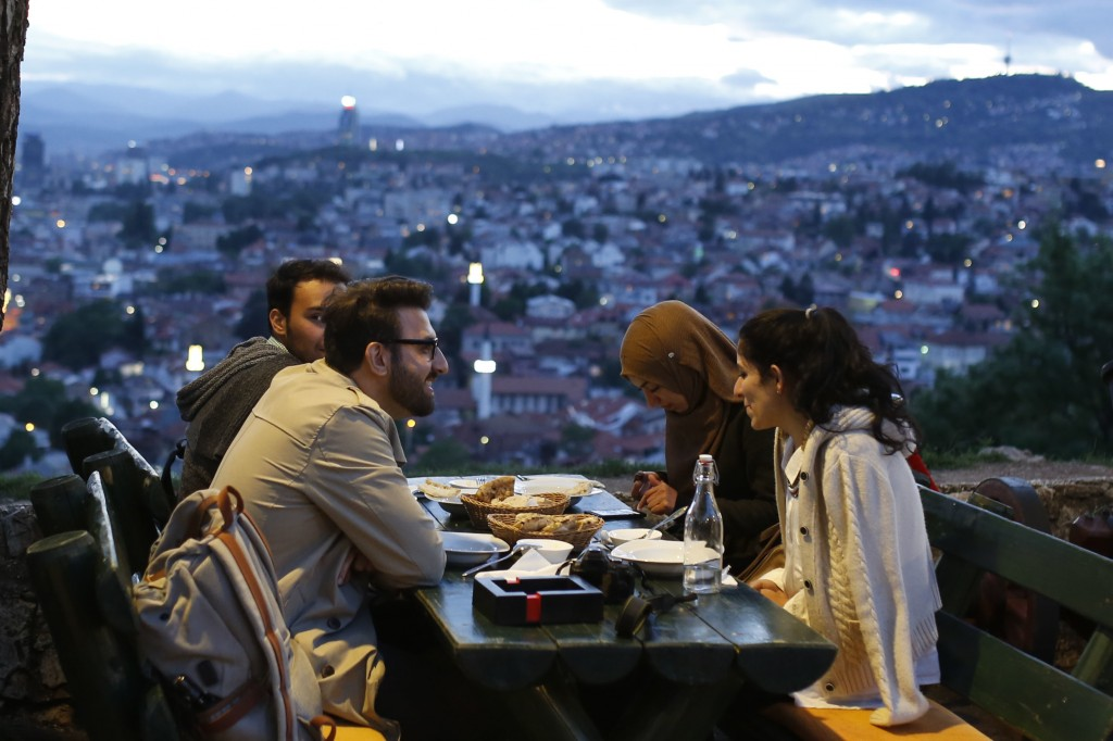A group of people break their fast on the first day of the fasting month of Ramadan, on an old fortress overlooking the historic center of Sarajevo, B...