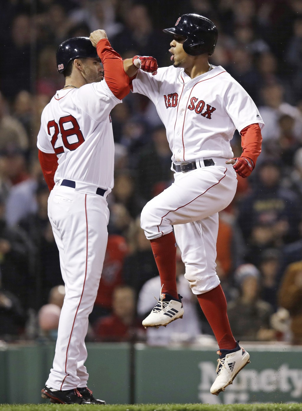 Boston Red Sox's Xander Bogaerts, right, is congratulated by J.D. Martinez as he crosses home plate after his three-run home run off Oakland Athletics