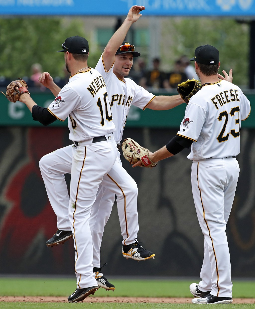 Pittsburgh Pirates' Adam Frazier, center, celebrates with Jordy Mercer (10), and David Freese (23) after the final out of a 3-2 win over the Chicago W