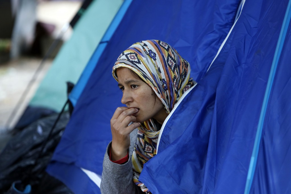 A migrant women from Afghanistan peers from the tent in the park across from The City Hall, in Sarajevo, Bosnia, Thursday, May 17, 2018. Thousands of