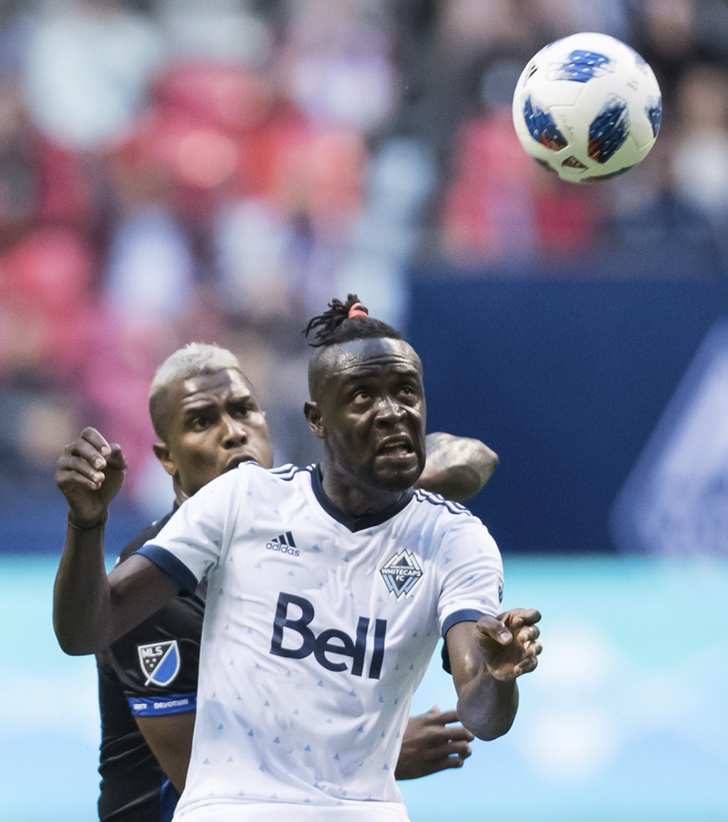 Vancouver Whitecaps' Kei Kamara, front, heads the ball as San Jose Earthquakes' Harold Cummings defends during the first half of an MLS soccer match i