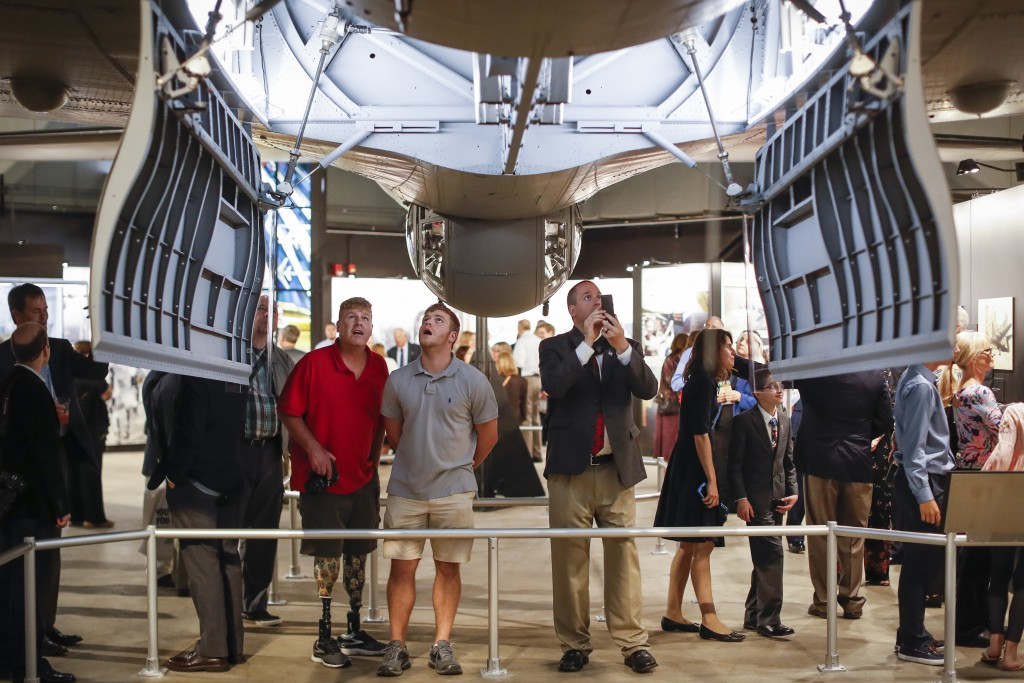 """Visitors gather under open bomb-bay doors during a private viewing of the Memphis Belle, a Boeing B-17 """"Flying Fortress,"""" at the National Museum of th"""