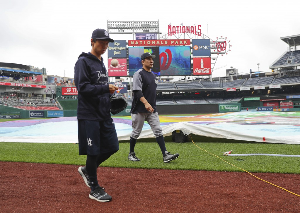 New York Yankees starting pitcher Masahiro Tanaka, center, and his translator, Shingo Horie, left, walk off the field at Nationals Park after it was a