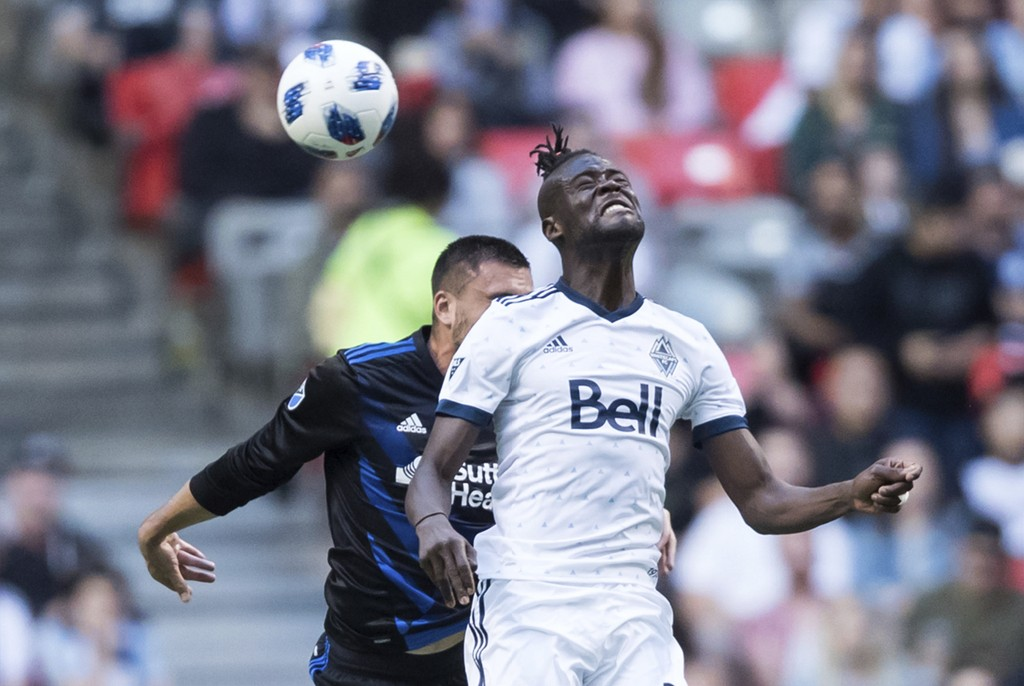 Vancouver Whitecaps' Kei Kamara, front, and San Jose Earthquakes' Jimmy Ockford vie for a head ball during the first half of an MLS soccer match in Va