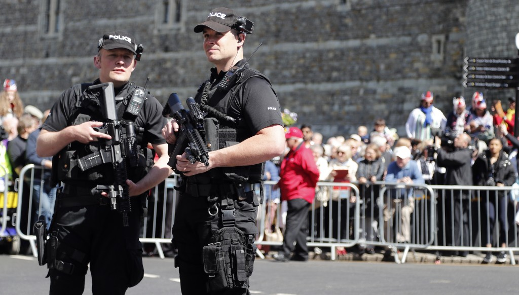 Armed police officers patrol in front of Windsor Castle before a rehearsal for the procession of the upcoming wedding of Britain's Prince Harry and Me