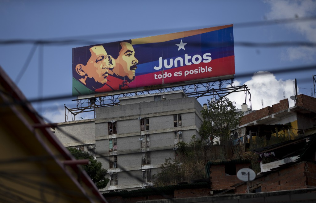 "An election campaign billboard shows Venezuela's late President Hugo Chavez, left, with President Nicolas Maduro and the Spanish phrase ""Together ever"