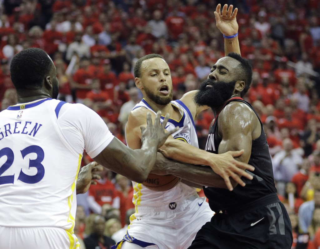 Houston Rockets guard James Harden, right, is fouled by Golden State Warriors guard Stephen Curry, center, during the second half in Game 2 of the NBA