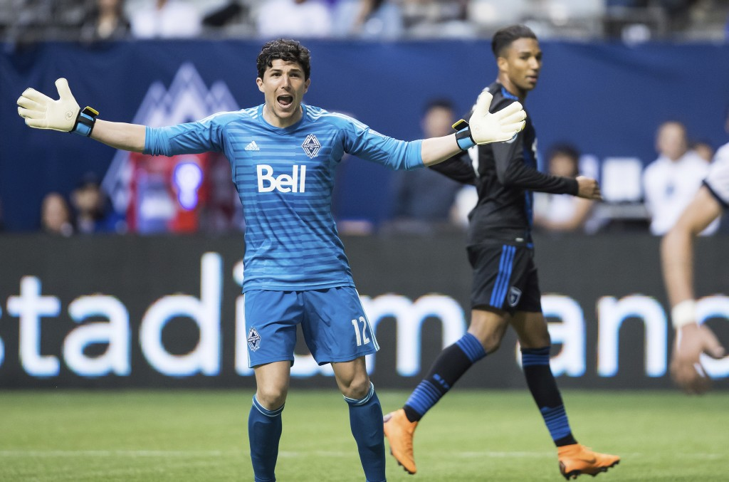 Vancouver Whitecaps goalkeeper Brian Rowe, front, reacts after San Jose Earthquakes' Danny Hoesen, back right, scored during the first half of an MLS