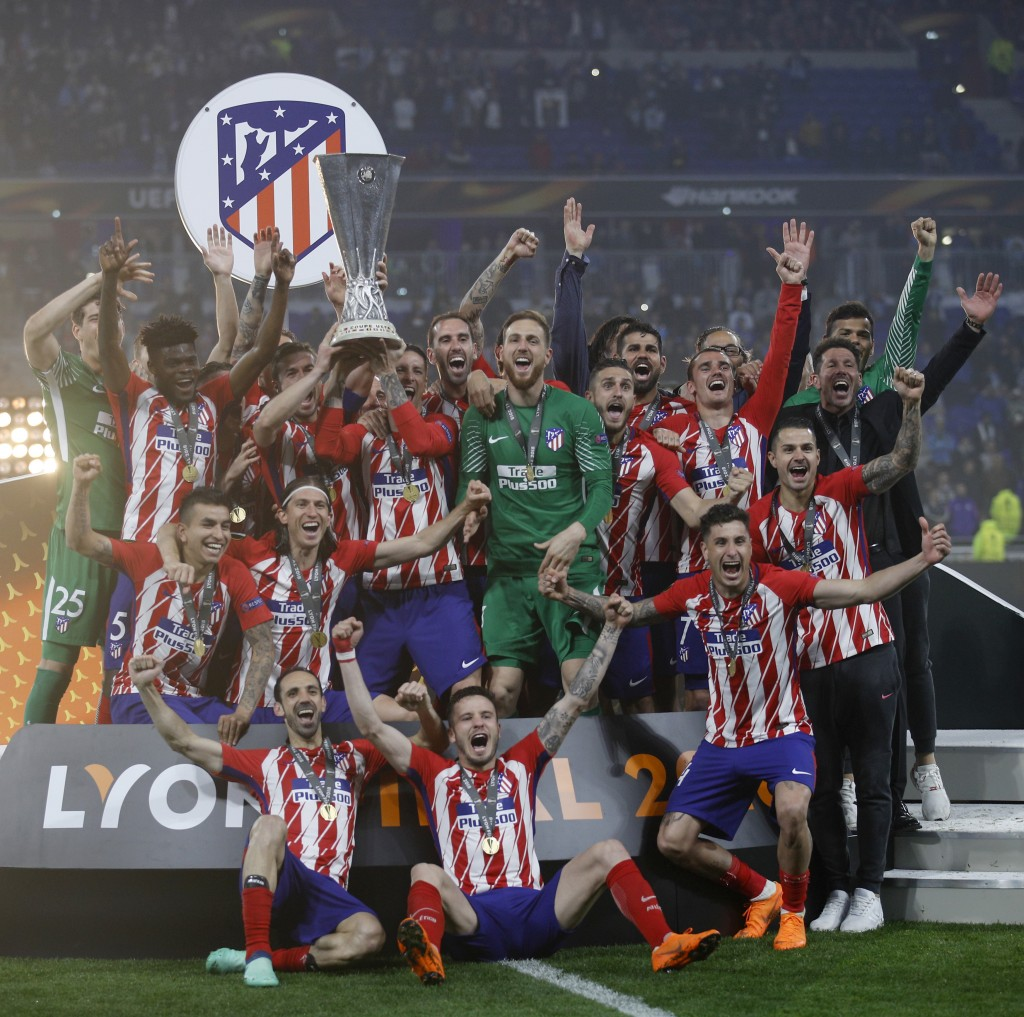 Atletico players with head coach Diego Simeone, far right in black, celebrate with the trophy after winning the Europa League Final soccer match betwe