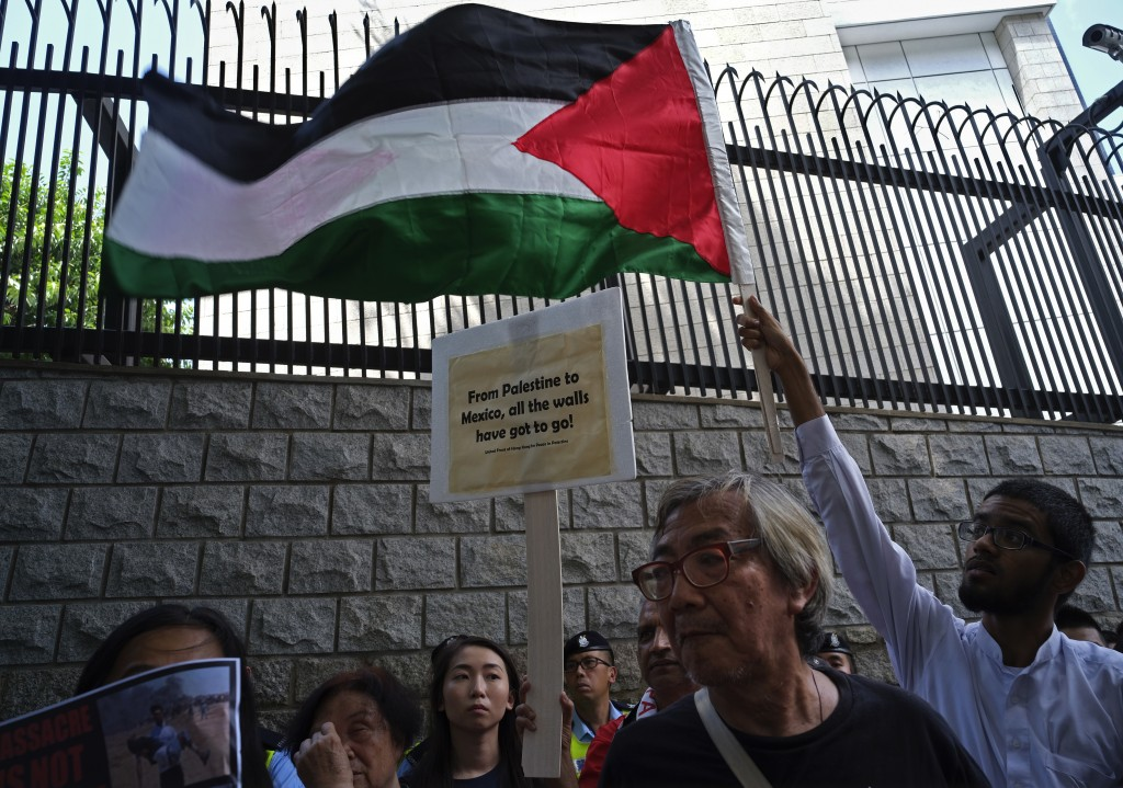 A protester displays a Palestinian flag as they march outside the U.S. Embassy to condemn the Gaza Strip violence which left dozens dead, in Hong Kong