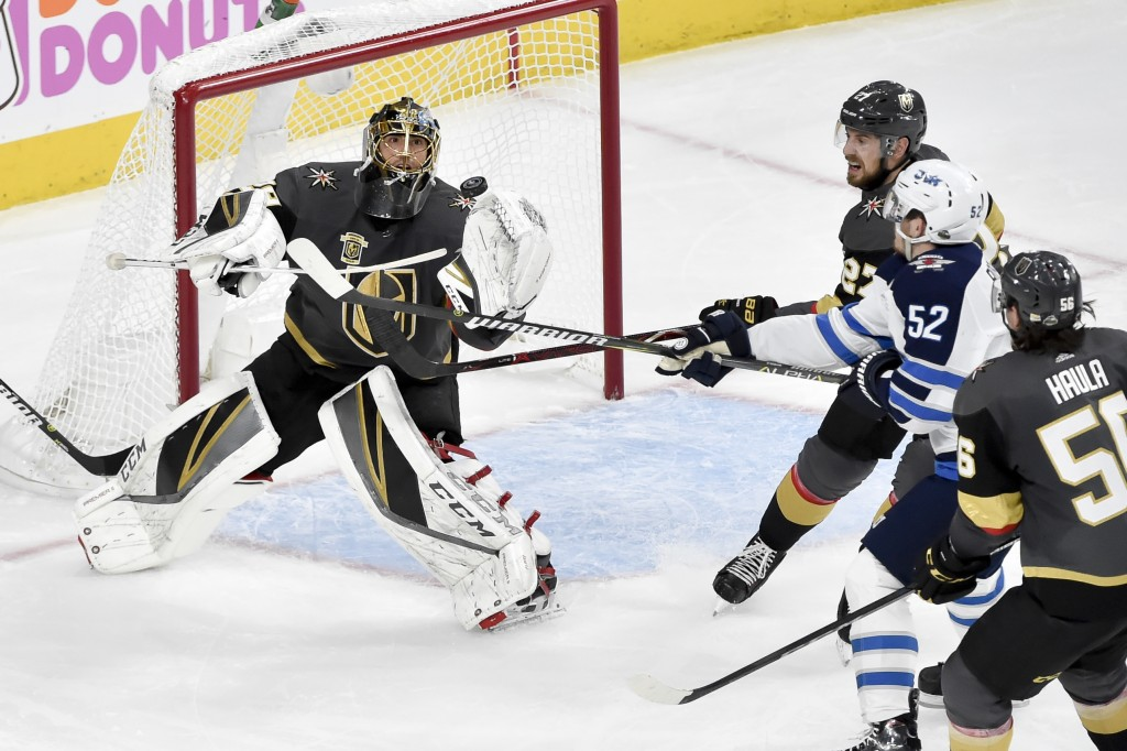 Vegas Golden Knights goaltender Marc-Andre Fleury, left, blocks a shot by Winnipeg Jets center Jack Roslovic during the second period of Game 3 of the