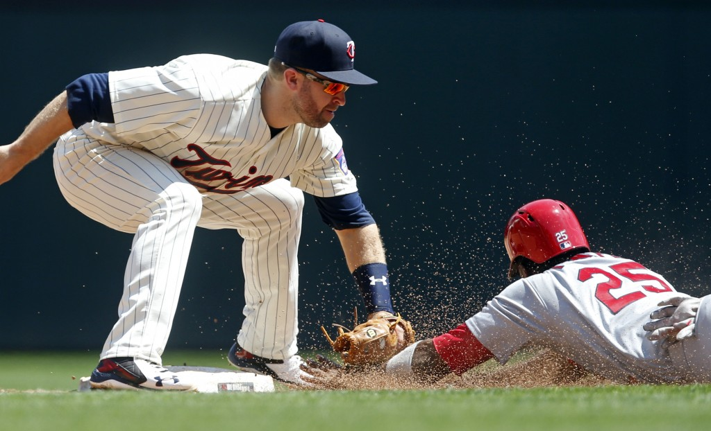 Minnesota Twins' second baseman Brian Dozier tags out St. Louis Cardinals' Dexter Fowler during a steal attempt in the third inning of a baseball game...
