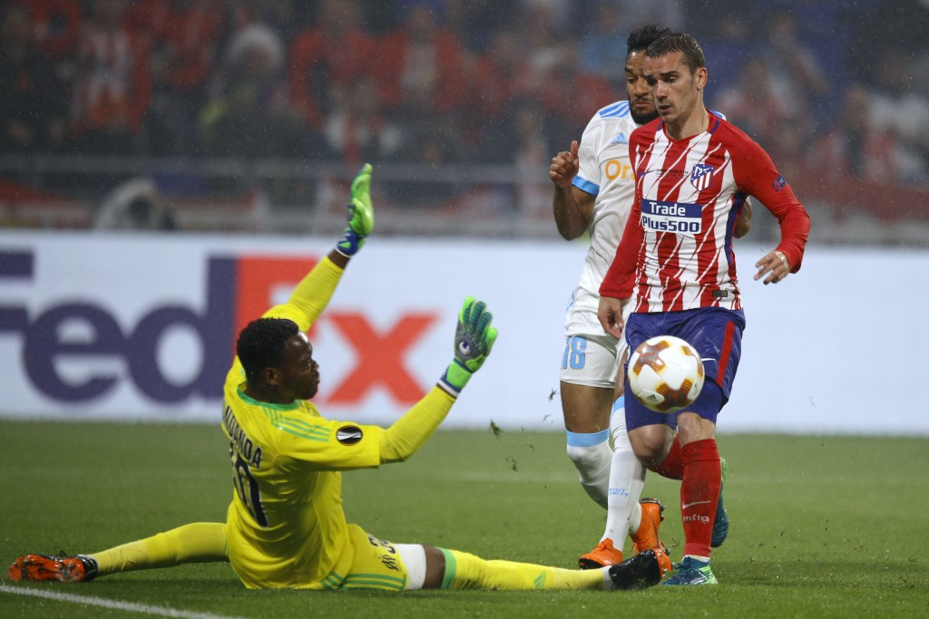 Atletico's Antoine Griezmann, right, scores 2-0 passing Marseille's goalkeeper Steve Mandanda, left, and Marseille's Jordan Amavi, rear, during the Eu
