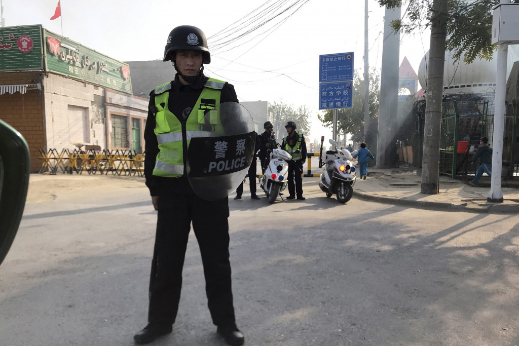 FILE - In this Nov. 2, 2017, file photo, a policeman holding shield and baton guards a security post leading into a center locals say is used for poli