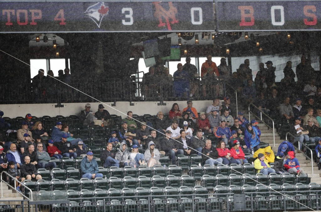 Fans take cover from the rain during the fourth inning of a baseball game between the New York Mets and the Toronto Blue Jays Wednesday, May 16, 2018,