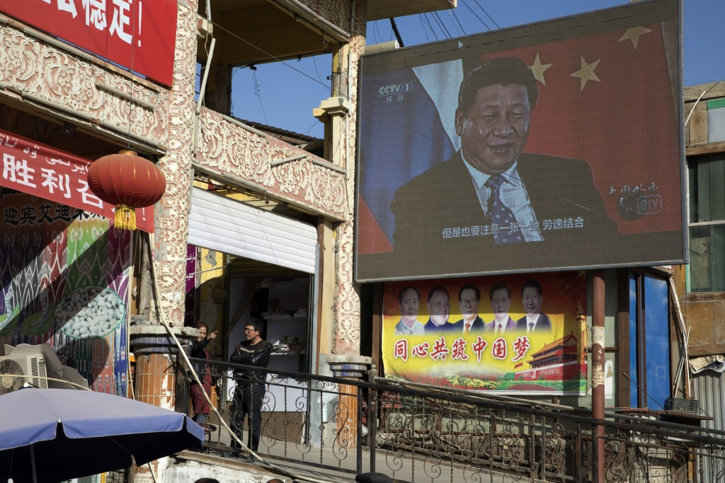 In this Nov. 3, 2017, photo, residents chat near a tv screen showing Chinese President Xi Jinping in Hotan in western China's Xinjiang region. Since 2