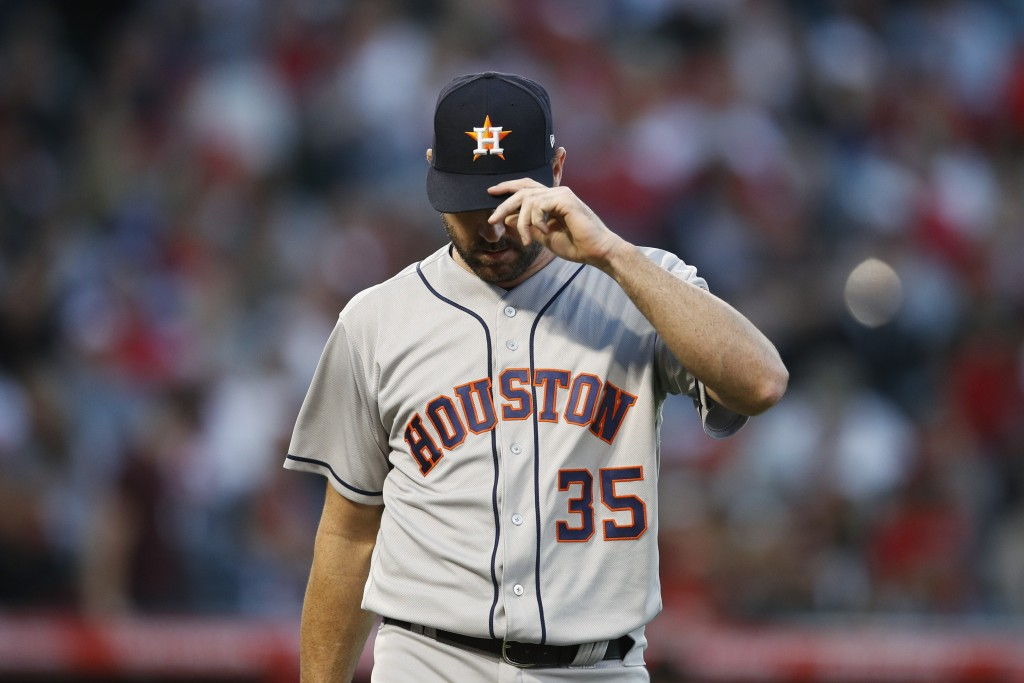 Houston Astros starting pitcher Justin Verlander adjusts his hat as he walks toward the dugout after the third inning of the team's baseball game agai